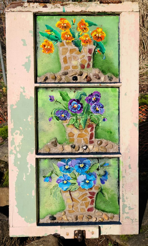 Hand-painted acrylic pansies with mosaic garden ground and pots. Mixed media decoration for a covered outdoor area.
