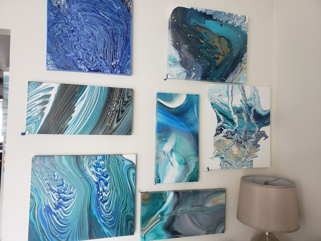 Several acrylic pour abstracts in shades of blue and green on a white wall. Artist: Brandon Brooks.
